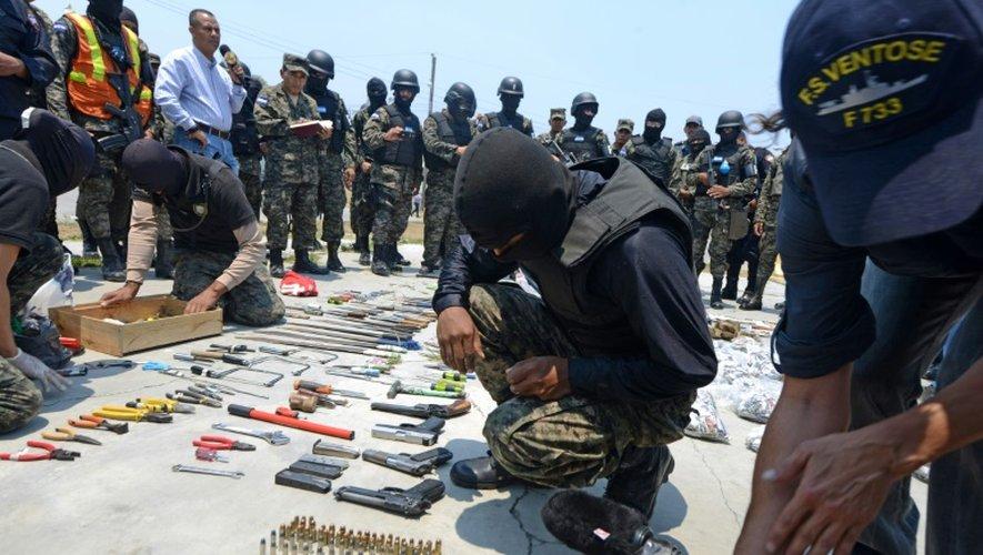 """Des policiers masqués présentent notamment des armes, munitions et de la drogue saisies dans les cellules du pénitentier de """"Marco Aurelio Soto"""" de Tamara situé au nord de Tegucigalpa au Honduras, le 24 avril 2015"""