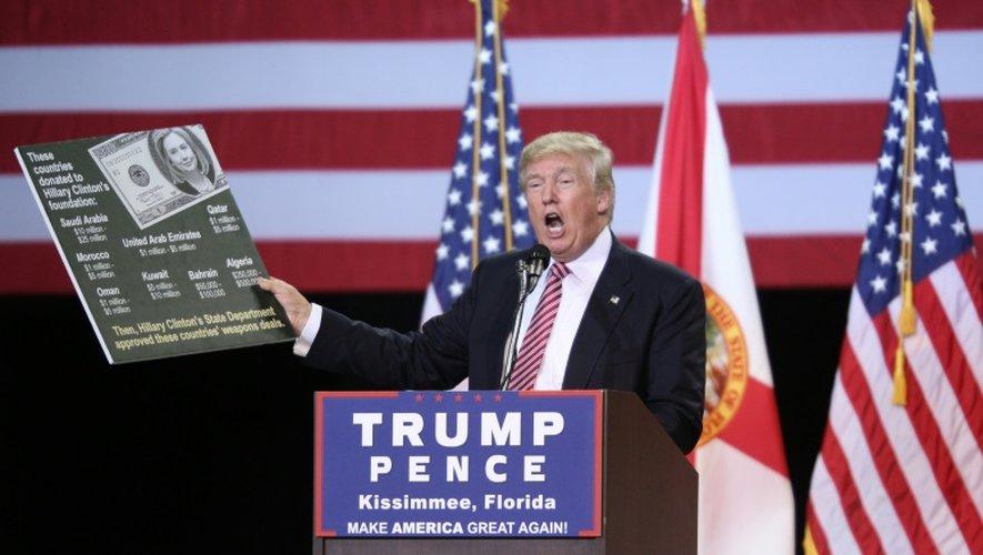 Donald Trump brandit une pancarte énumérant les pays arabes ayant contribué à la fondation Clinton, lors d'un meeting de campagne, le 11 août 2016 à Kissimmee en Floride
