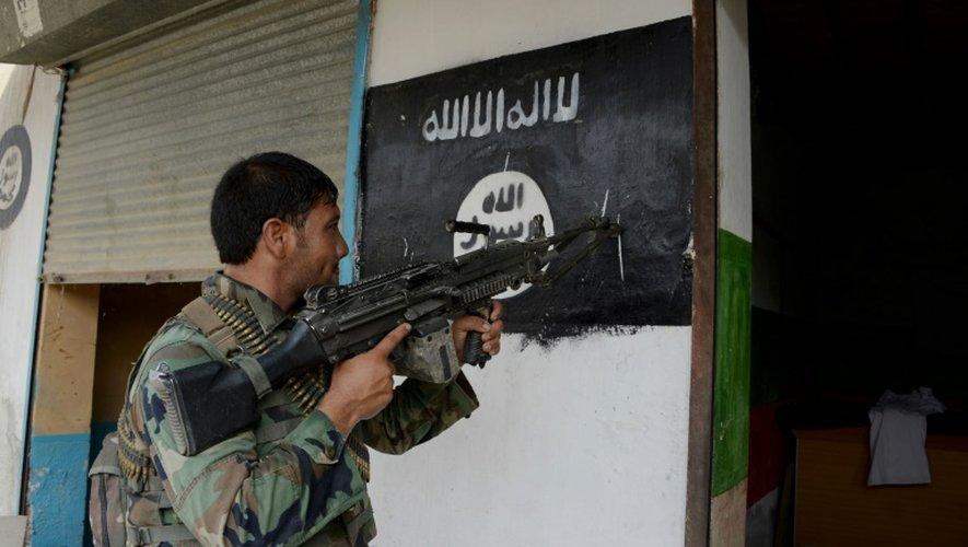Un soldat de l'armée afghane pointe son arme sur un drapeau du groupe Etat islamique peint sur un mur à Kot, dans l'est de l'Afghanistan, le 26 juillet 2016