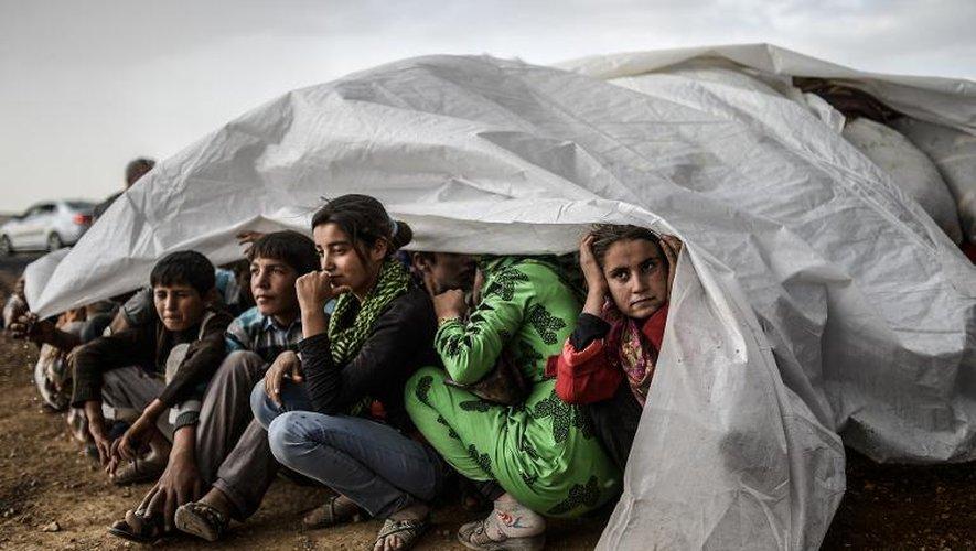 Des réfugiés syriens kurdes s'abritent de la pluie à Suruc, dans la province de Sanliurfa, après avoir franchi la frontière entre la Syrie et la Turquie, le 2 octobre 2014