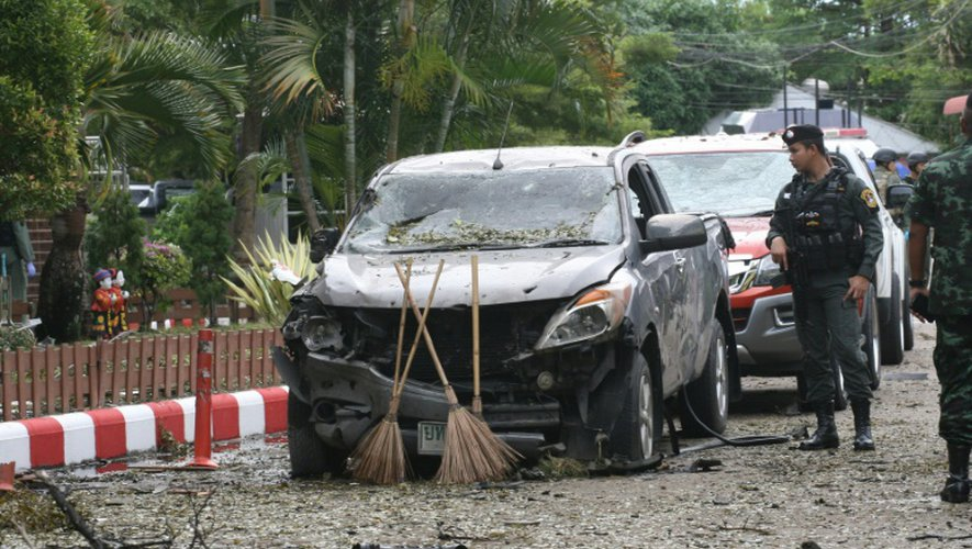 Un soldat thaïlandais inspecte une voiture carbonisée là où une bombe a explosé, à l'extérieur d'un hôtel dans la province de Pattani (sud), le 24 août 2016