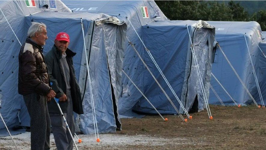 Deux hommes près des tentes installés pour les victimes du séisme dans le village d'Illica, dans le centre de l'Italie, le 25 août 2016