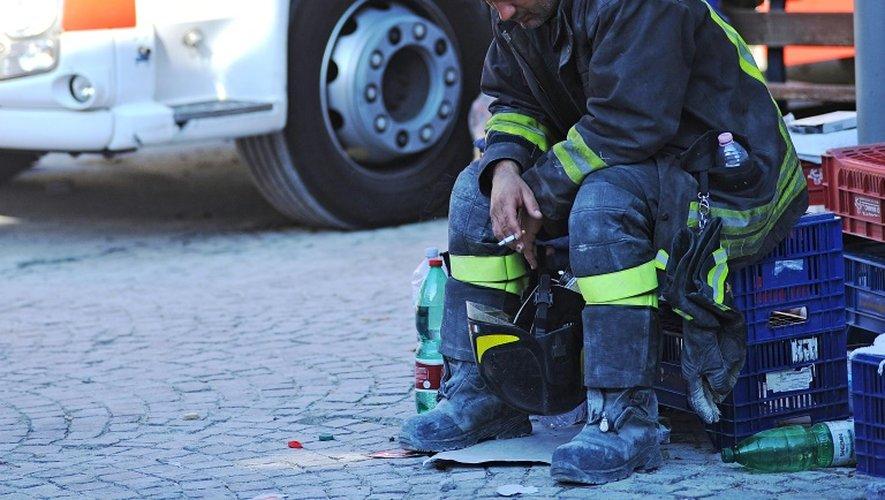 Un pompier se repose pendant les opérations de secours à Amatrice, le 24 août 2016 dans le centre de l'Italie
