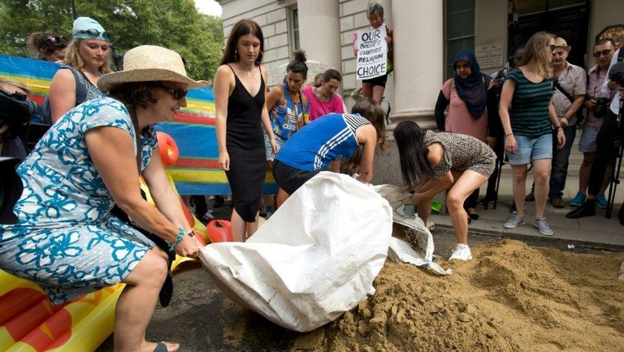 Des manifestantes installent une fausse plage devant l'ambassade de France à Londres pour protester contre l'interdiction du burkini, le 25 août 2016