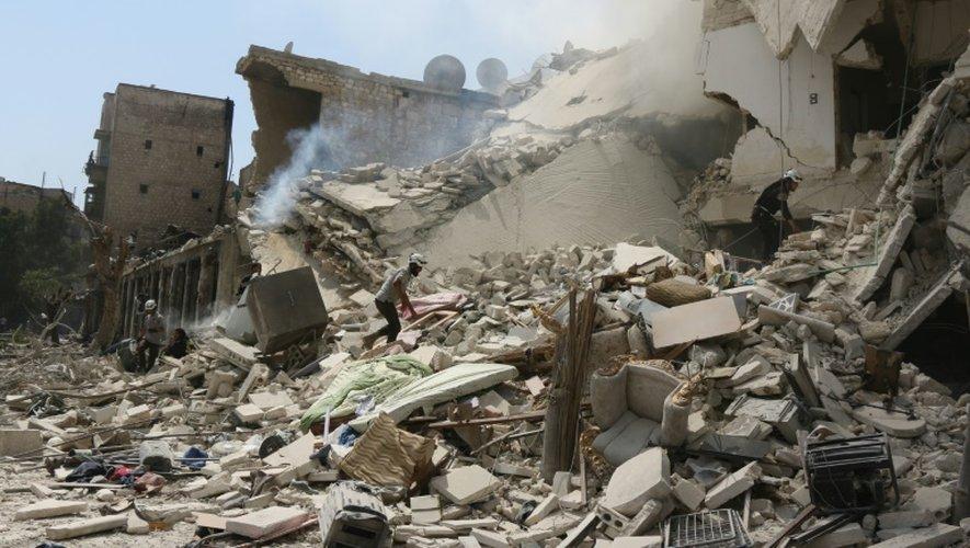 Des secouristes syriens cherchent des victimes dans les décombres d'un immeuble attaqué avec des barils d'explosifs, à Alep le 27 août 2016