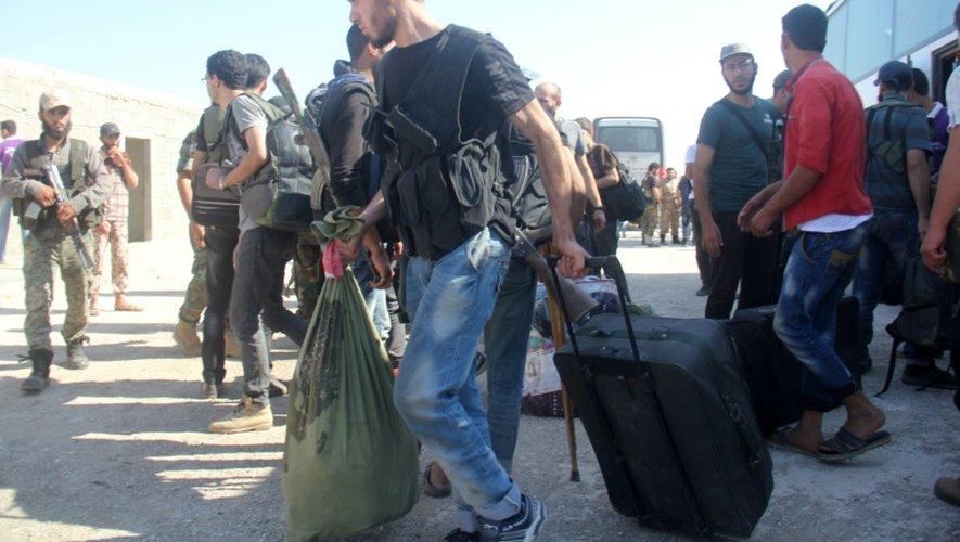 Des combattants rebelles et leurs familles arrivent à Idleb, le 27 août 2016 après été évacués de Daraya