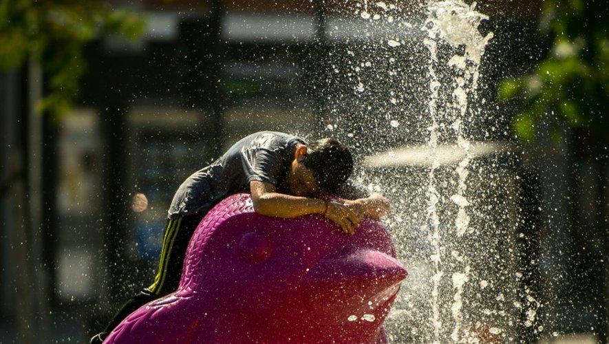 Un enfant se rafraîchit à une fontaine, à Calais le 25 août 2016