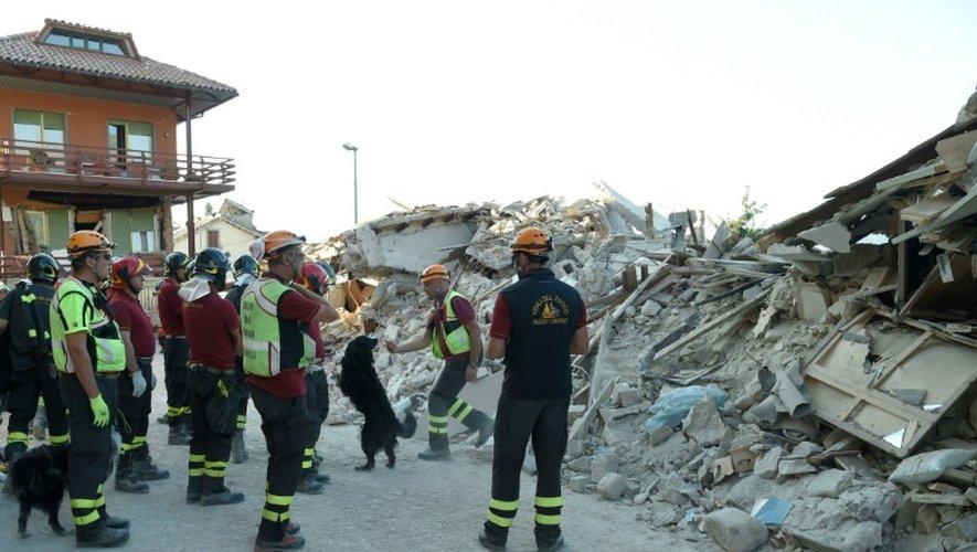 Des pompiers et leurs chiens inspectent les décombres, le 27 août 2016 à Amatrice, trois jours après le séisme