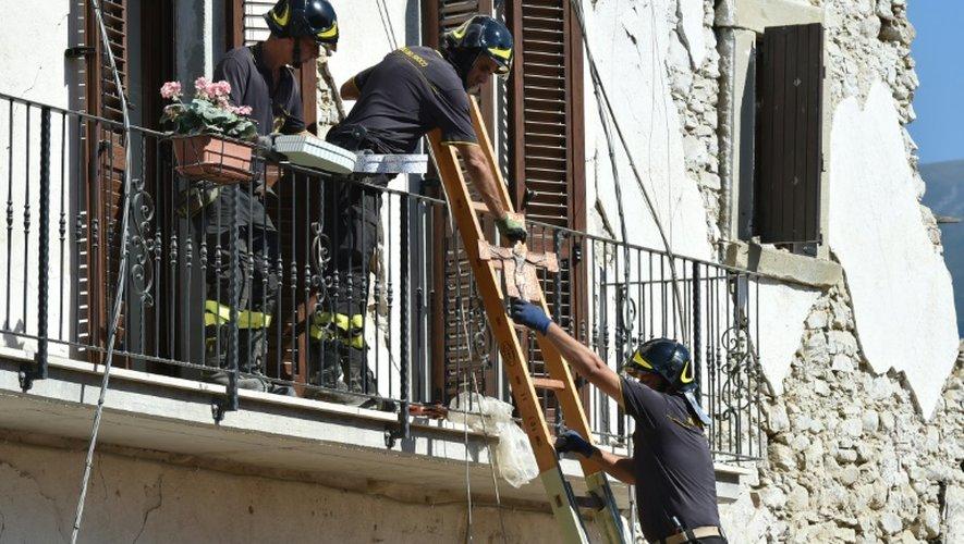 Des pompiers aident les habitants à récupérer leurs affaires personnelles dans les maisons endommagées par le séisme, le 28 août 2016 à Amatrice, dans le centre de l'Italie