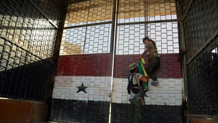 Des combattants accrochent le drapeau des YPG - Unités de protection du peuple kurde - sur le portail de la prison de Hassaké, dans le nord-est de la Syrie, le 23 août 2016