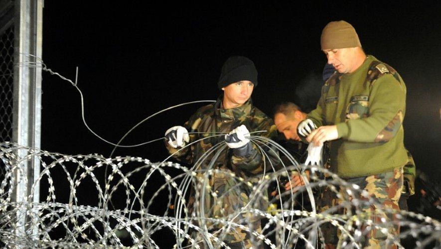 Soldats et policiers hongrois achèvent de mettre les derniers barbelés pour fermer la frontière entre la Hongrie et la Croatie à Botovo, le 16 octobre 2015