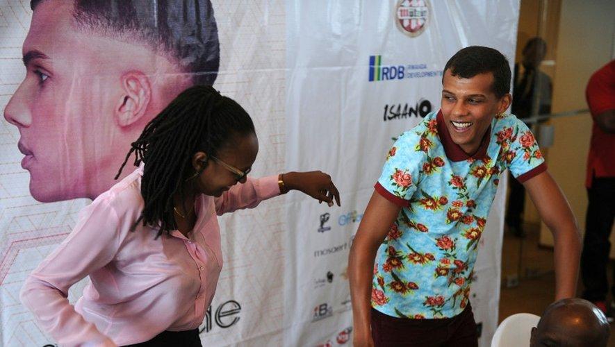 Le chanteur belge Stromae fait un pas de danse avec l'une des ses cousines lors d'une conférence de presse à Kigali le 17 octobre 2015