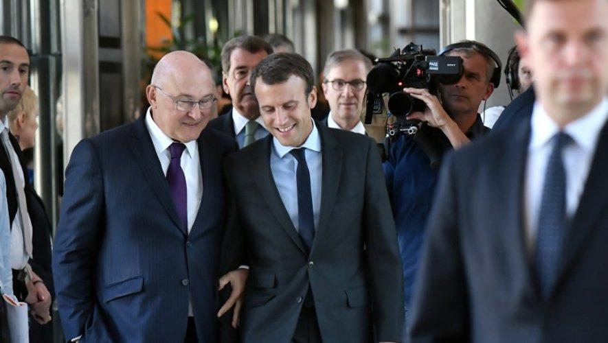 Michel Sapin et Emmanuel Macron Michel à leur arrivée à la cérémonie de la passation de pouvoirs le 31 août 2016 à Bercy à Paris
