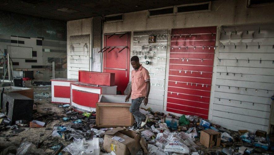 Un employé au milieu des débris d'un magasin pillé lors des violences à Libreville, le 1er septembre 2016 au Gabon