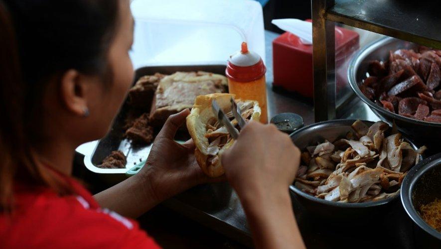 Préparaion d'un sandwich appelé banh-mi à Hanoï, le 31 août 2016