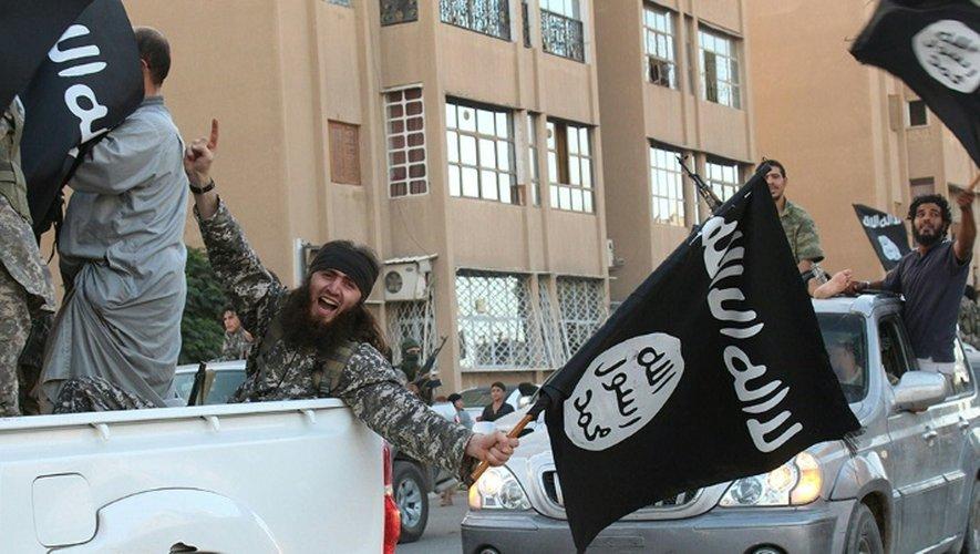 Une image diffusée par l'organe de presse jihadiste Welayat Raqa le 30 juin 2014 montre un membre du groupe État islamique (EI) défila un drapeau de l'EI à la main dans une rue de la ville syrienne de Raqa.