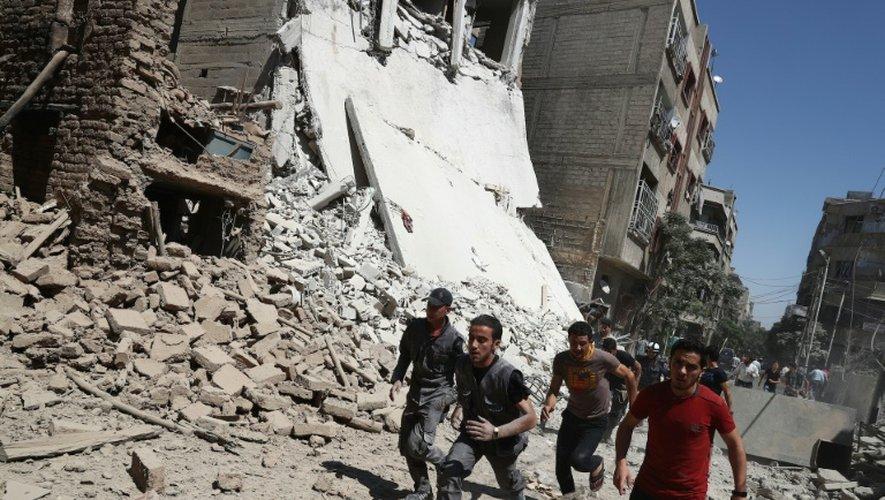 Des Syriens courent se mettre à l'abri lors de frappes aériennes du régime sur la ville de Douma, le 9 septembre 2016
