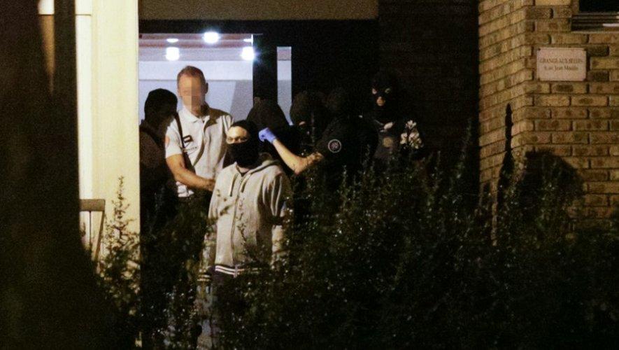 Une femme, la tête recouverte d'une couverture, est emmenée   par les policiers le 8 septembre 2016 à Boussy-Saint-Antoine