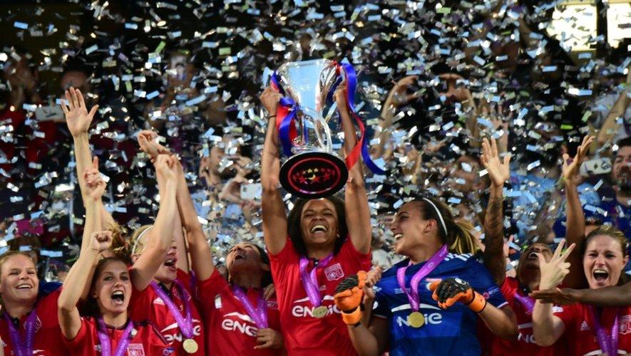 La capitaine de l'Olympique de Lyon Wendie Renard brandit le trophée après la victoire face à Wolfsburg en finale de Ligue des champions, le 26 mai 2016 à Reggio Emilia (Italie)