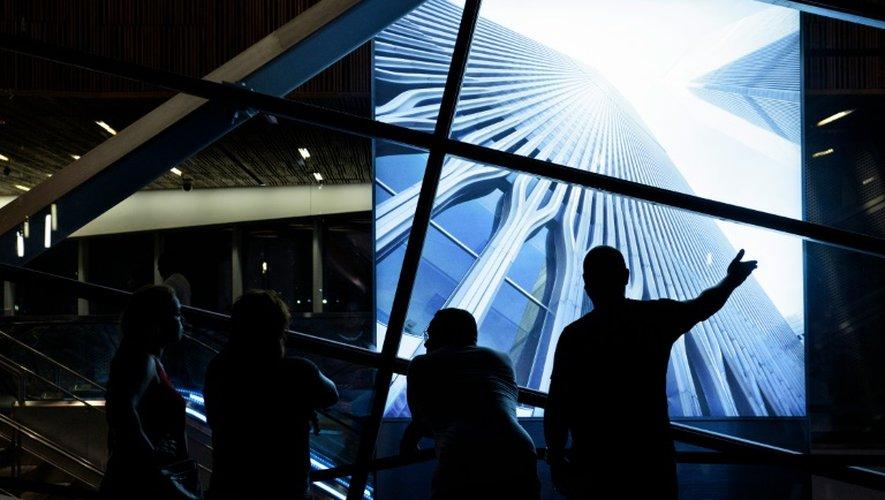Des personnes regardent une photo des tours jumelles du World Trade Center détruites le 11 septembre 2001, sur le site de Ground Zero le 10 septembre 2016 à New York