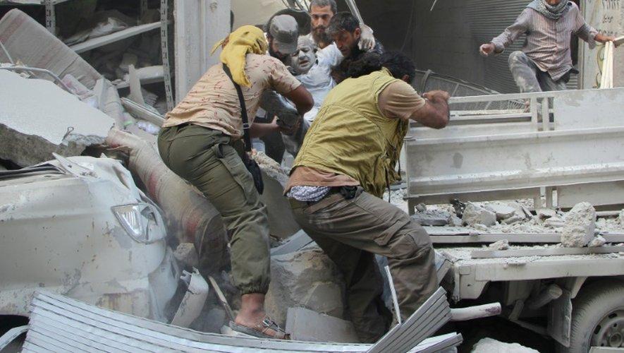 Des habitants de la ville syrienne rebelle d'Idleb évacuent un blessé des décombres d'un immeuble après des raids aériens du régime, le 10 septembre 2016