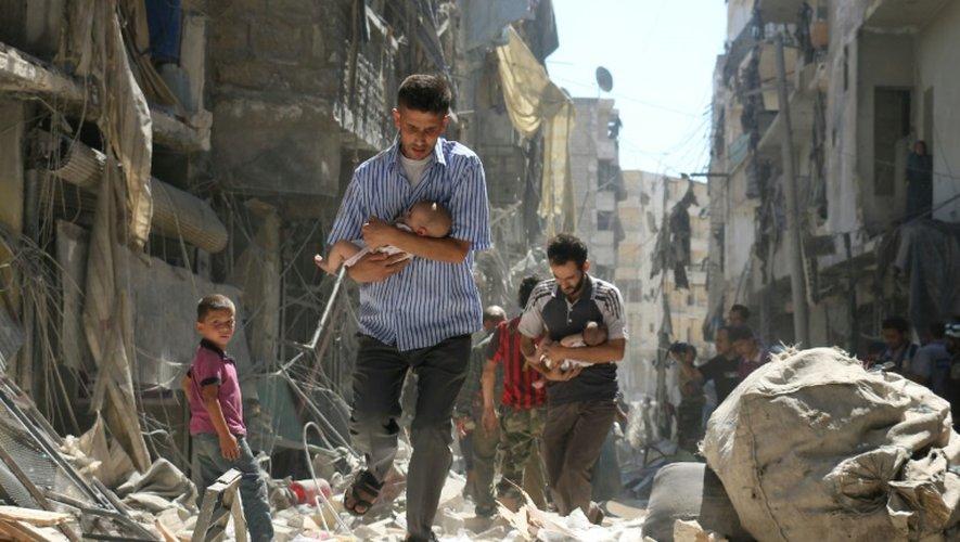 Des Syriens portent des bébés dans leurs bras à travers les ruines après des raids aériens sur un quartier rebelle d'Alep, le 11 septembre 2016