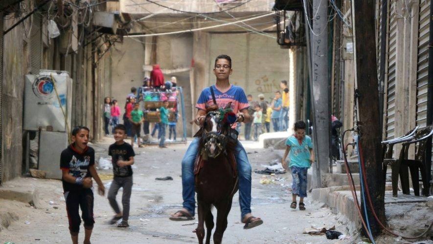 Un garçon syrien monte un cheval dans les rues d'Alep et des enfants jouent lors de l'Aïd au premier jour de la trêve, le 13 septembre 2016