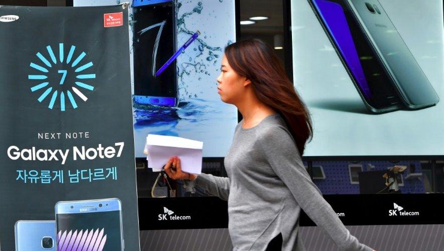 Une femme passe devant des affiches montrant un Galaxy Note 7 et un Galaxy S7 d'un magasin à Séoul, le 12 septembre 2016