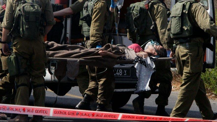 Des soldats Israéliens transportent une civile blessée par un Palestinien lors d'une attaque à la voiture bélier près de la colonie israélienne de Kyriat Arba, en Cisjordanie occupée, le 16 septembre 2016