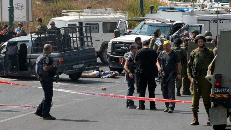 Les forces de l'ordre israéliennes entourent le corps du palestinien auteur d'une attaque à la voiture bélier à un arrêt de bus près de la colonie israélienne de Kyriat Arba, en Cisjordanie occupée,le 16 septembre 2016