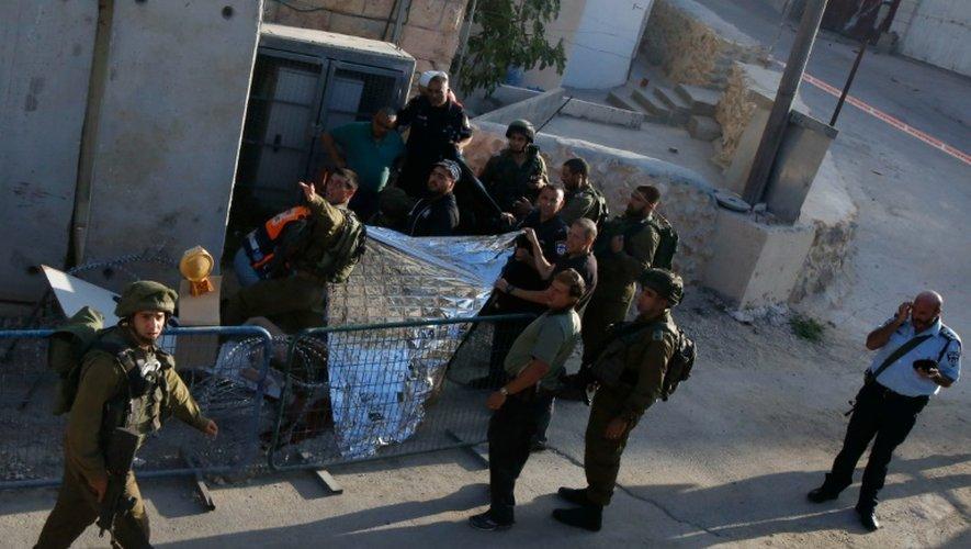 Des soldats israéliens recouvrent le corps d'un Palestinien abattu à Hébron après avoir blessé un soldat, dans le sud de la Cisjordanie occupée, le 16 septembre 2016
