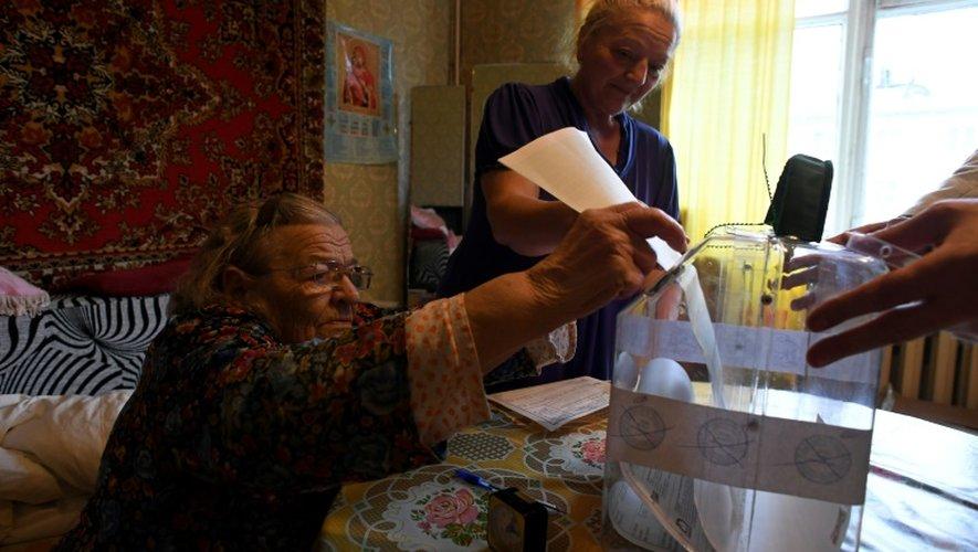 Une personne âgée dépose son bulletin de vote dans une urne apportée à son domicile à Moscou