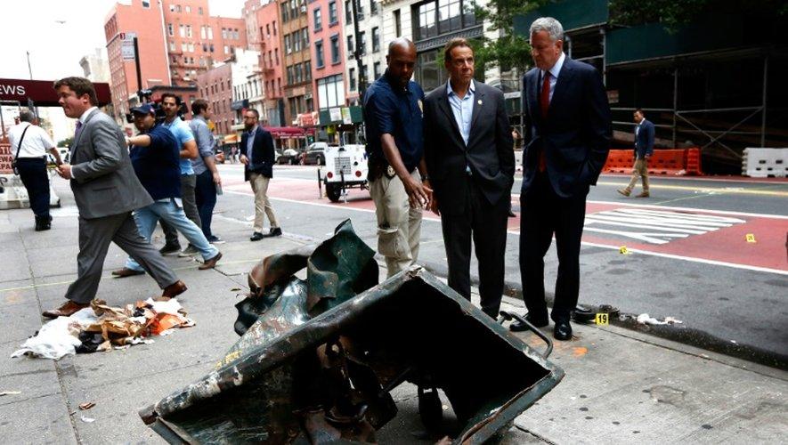 Le maire de New York Bill de Blasio et le gouverneur de New York Andrew Cuomo le 18 septembre 2016 devant une benne à ordures déchiquetée par l'explosion survenue la veille à New York