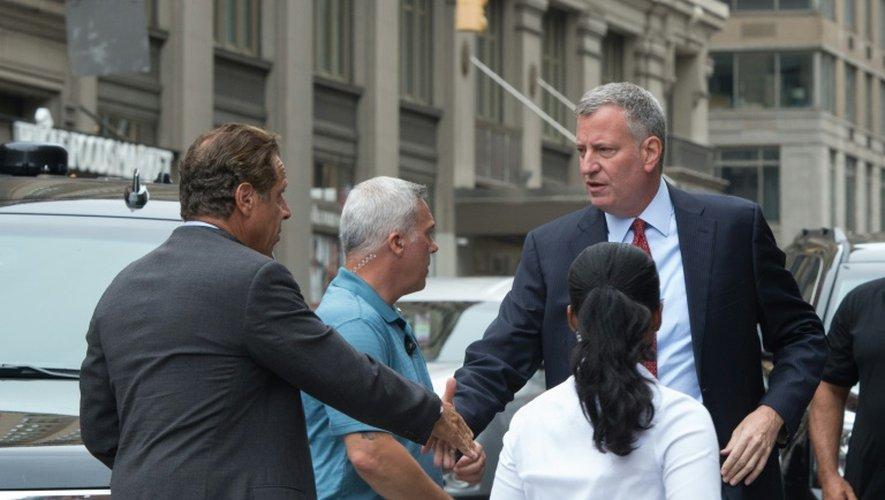 Le gouverneur de New York Andrew Cuomo (g) et le maire de la ville Bill de Blasio (d) se saluent sur le lieu de l'explosion à New York, le 18 septembre 2016