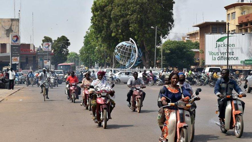 Des habitants de Ouagadougou circulent dans une rue de la capitale, le 7 novembre 2014 au Burkina Faso