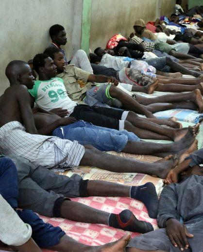 Des migrants africains attendent dans un centre d'hébergement pour clandestins le 31 août 2016 dans le port de Zawiyah en Libye