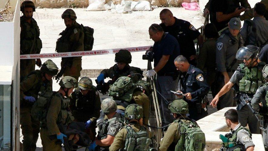 Des membres des forces de sécurité israéliennes évacuent un des Palestiniens abattus après une attaque au couteau, le 19 septembre 2016, près du Tombeau des Patriarches, à Hébron