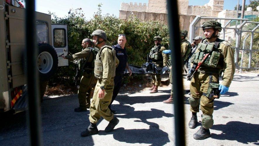 Des membres des forces de sécurité israéliennes transportent le corps d'un Palestinien abattu après une attaque au couteau, le 19 septembre 2016, à Hébron