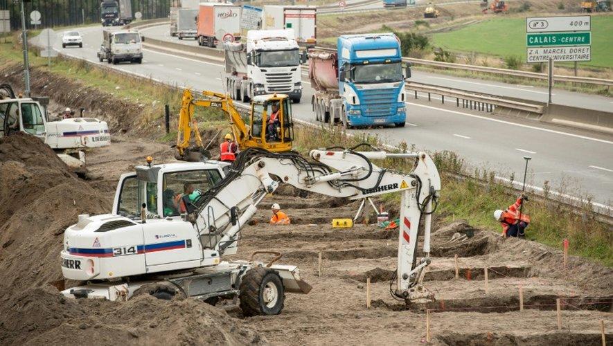 Des ouvriers creusent les fondations d'un mur destiné à empêcher l'intrusion de migrants sur la rocade portuaire de Calais, le 20 septembre 2016