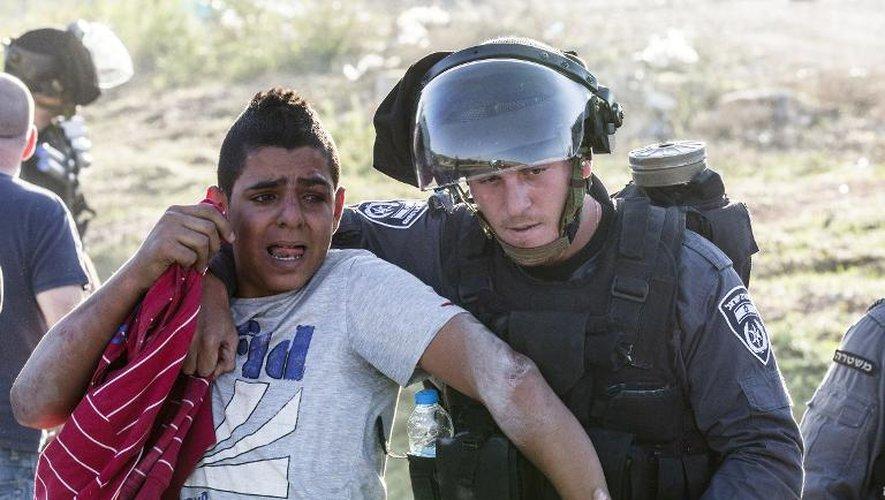 Un policier israélien maîtrise un jeune arabe-israélien lors d'affrontements dans le village de Kfar Kana (nord d'Israël), le 9 novembre 2014