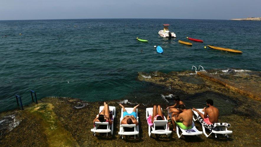 Des Libanais prennent un bain de soleil au bord de la mer à Anfeh, au nord de Beyrouth, le 23 août 2016