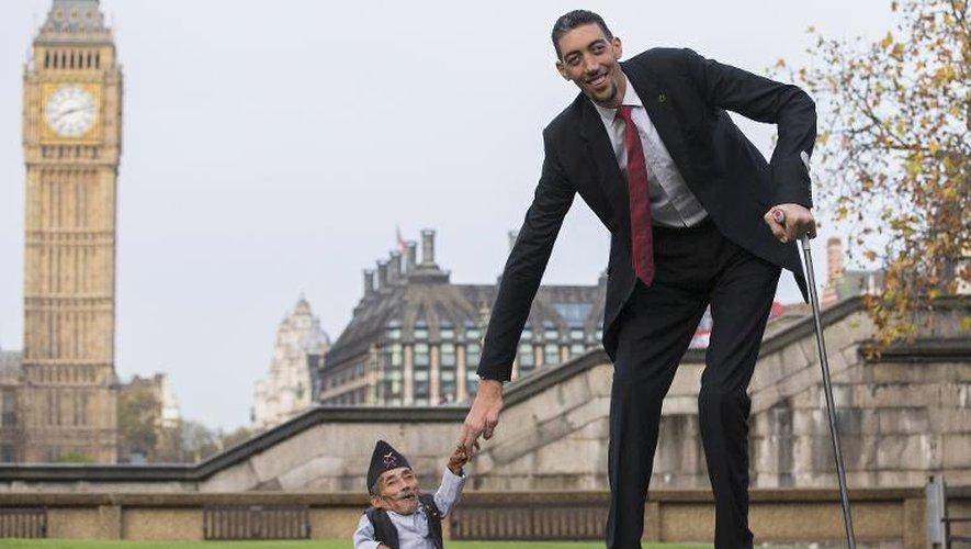 Le Népalais Chandra Bahadur Dangi (g), l'homme le plus petit du monde selon le Guinness Book des records, pose aux côtés de l'homme le plus grand du monde, le Turc Sultan Kosen, à Londres le 13 novembre 2014