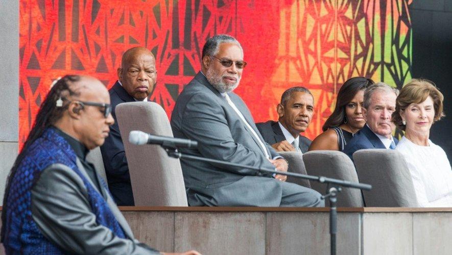 Stevie Wonder chante en présence de Barack Obama (au c.) et de son prédécesseur Georges W. Bush (2e à d.) lors de l'inauguration du Musée dédié à la culture afro-américaine, le 24 septembre 2016 à Washington