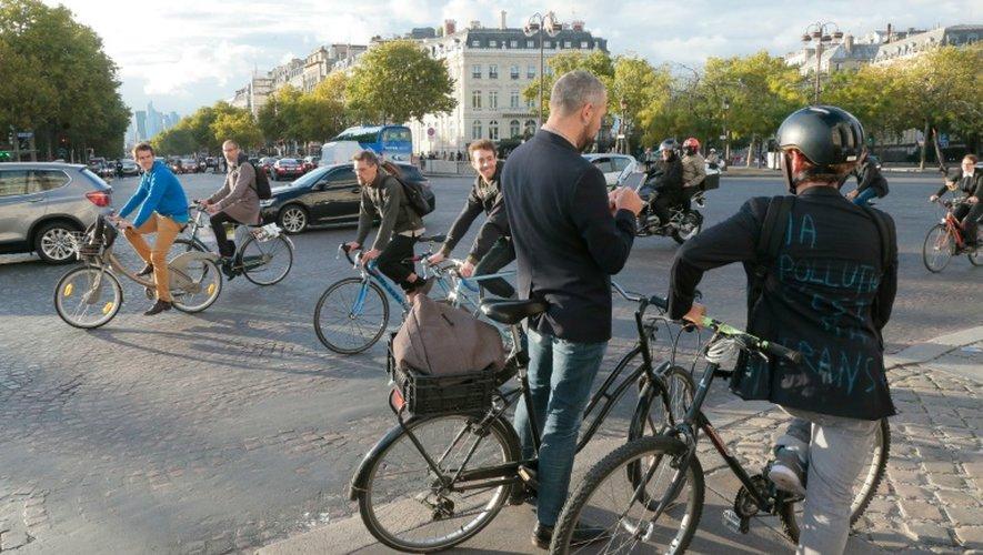 """Des cyclistes circulent près de l'Arc de Triomphe le 22 septembre 2015 à l'appel du mouvement """"Velorution"""" en prélude à la journée sans voiture du 27 septembre 2015 à Paris"""