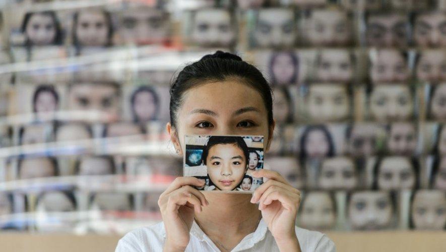Une jeune femme montre une photo d'elle-même et du changement de son visage après une épilation de ss sourcils, le 22 juillet 2016 à Hong Kong