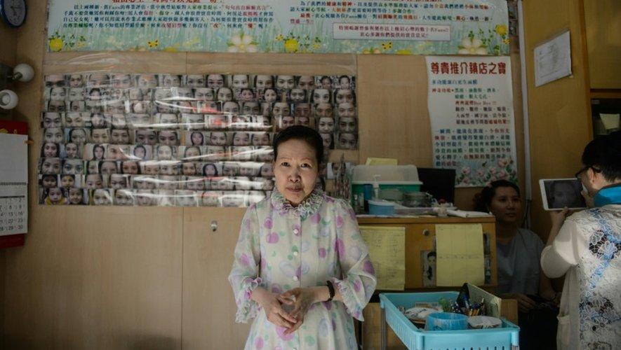 Li Chau-jing, spécialiste de l'art chinois de lire sur les visages, épile les sourcils de ses patients pour améliorer leurs chances dans la vie, le 22 juillet 2016 à Hong Kong