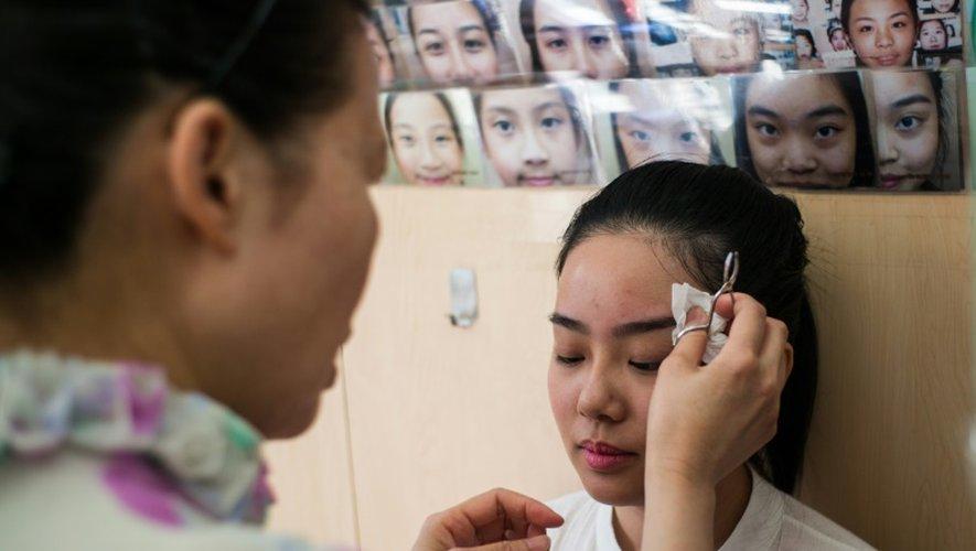 Li Chau-jing, spécialiste de l'art chinois de lire sur les visages, épile les sourcils d'une de ses patientes, le 22 juillet 2016 à Hong Kong