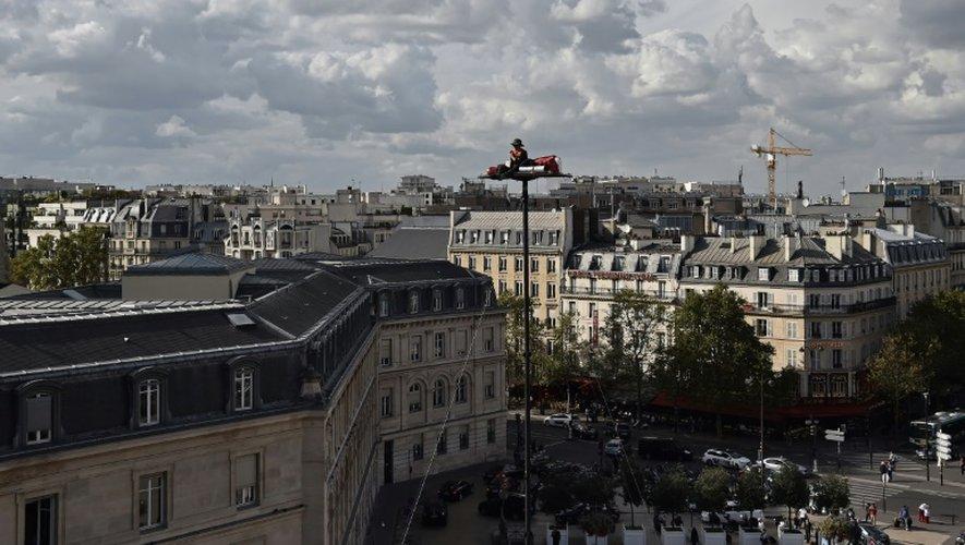 """L'artiste Abraham Poincheval, 44 ans, sur sa """"vigie"""", une plateforme de 90 cm sur 1,60 m, le 26 septembre 2016, face à la gare de Lyon à Paris."""