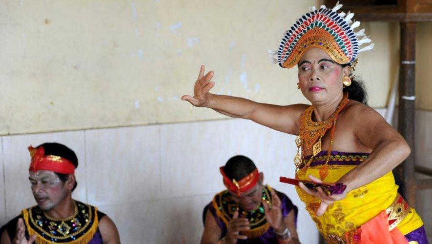 Des Balinaises en corsage doré dansent sur une musique traditionnelle devant des hommes assis par terre jambes croisées autour d'elles en remuant leurs mains. Un show dont tous les acteurs sont sourds