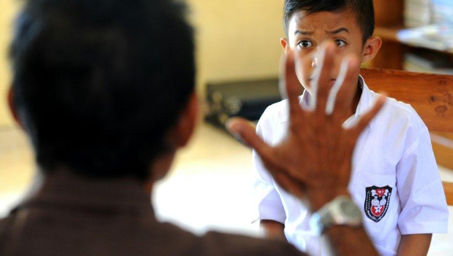 Un instituteur s'adresse à un élève sourd en langage des signes, le 20 juillet 2016 à Bengkala en Indonésie